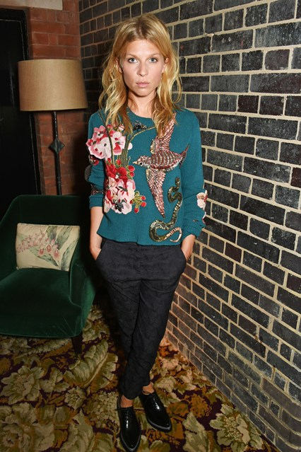 Clémence Poésy wearing flat shoes, black pants and a teal sweater with embroidered flowers, bird and snake